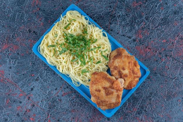 Een blauwe houten plank van noedels en kipkoteletten.