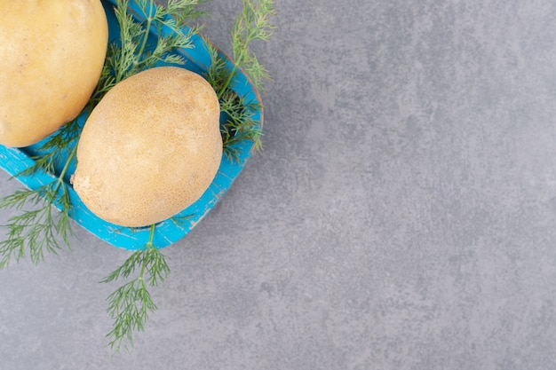 Een blauwe houten plank van ongekookte aardappelen met verse dille.