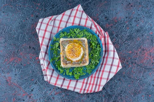Een blauwe houten plank van toast met ei en kruiden.