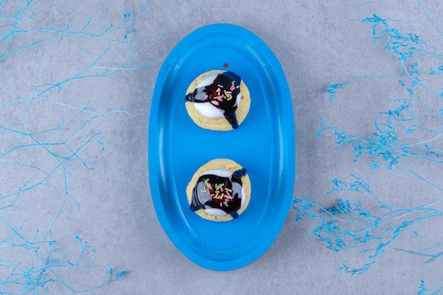 Een blauwe houten plank van zoete koekjes met kleurrijke hagelslag en chocoladesiroop