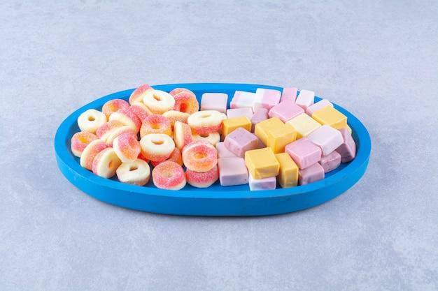 Een blauwe houten plank van zoete rode gelei snoepjes met zoete regenboog drop. hoge kwaliteit foto