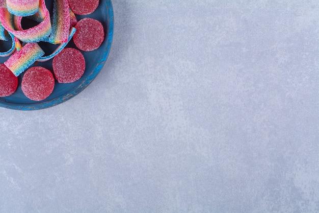 Een blauwe houten plank van zoete rode gelei snoepjes met zoete regenboog drop