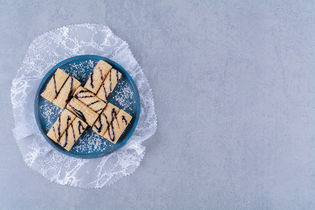 Een blauwe houten plank van zoete stokjes met hagelslag en chocoladesiroop
