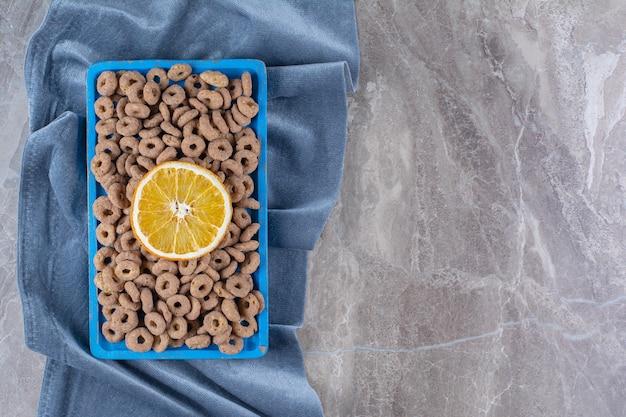 Een blauwe houten plank vol gezonde cornflakesringen met een schijfje sinaasappelfruit