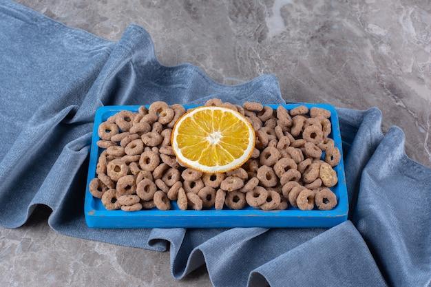 Een blauwe houten plank vol gezonde granenringen met een schijfje sinaasappelfruit.