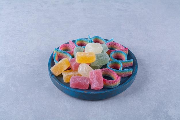 Een blauwe houten plank vol kleurrijke suikermarmelades