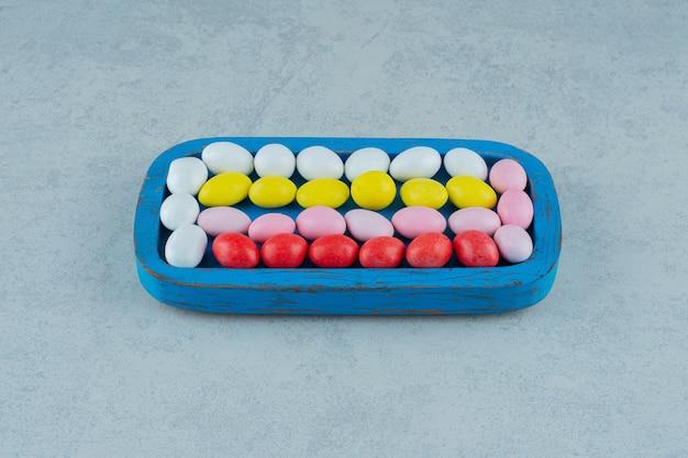 Een blauwe houten plank vol met ronde zoete kleurrijke snoepjes op een witte ondergrond