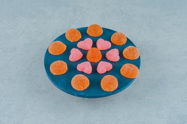Een blauwe houten plank vol oranje suikerachtige gelei-snoepjes met hartvormige gelei-snoepjes