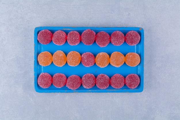 Een blauwe houten plank vol rode en oranje zoete marmelade