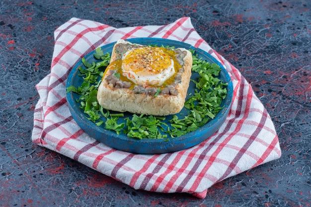 Een blauwe houten toastplank met ei en kruiden