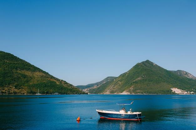 Een blauwe houten vissersboot afgemeerd in de baai van kotor nabij de stad perast in montenegro.