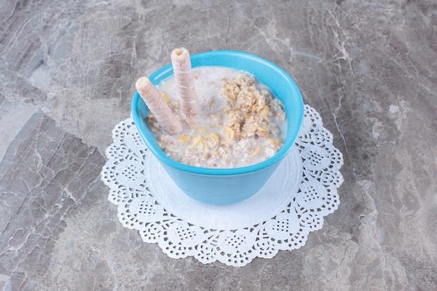 Een blauwe kom gezonde cornflakes met melk en zoete stokjes.
