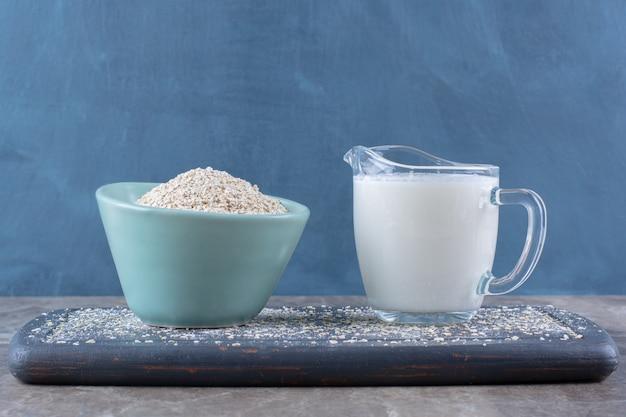 Een blauwe kom rijst met een glazen kopje melk op een houten bord.