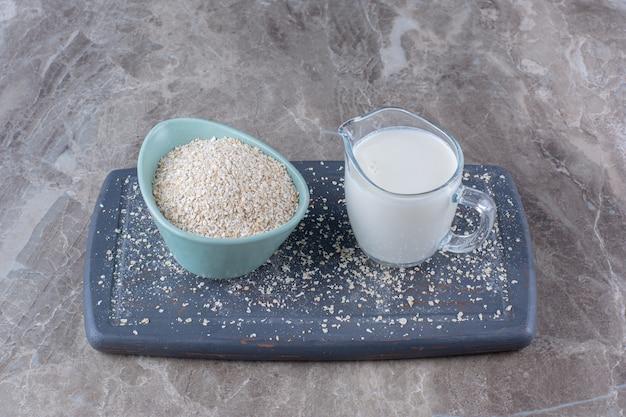 Een blauwe kom rijst met een glazen kopje melk op een houten bord