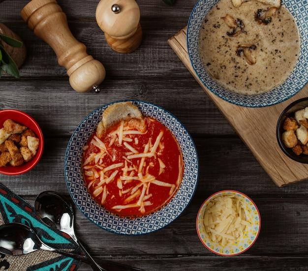 Een blauwe kom tomatensoep met fijngehakte parmezaanse kaas bovenop en champignonsoep eromheen