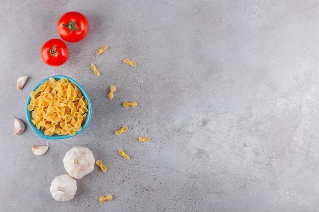 Een blauwe kom vol farfalle rauwe droge pasta met groenten op een stenen tafel.