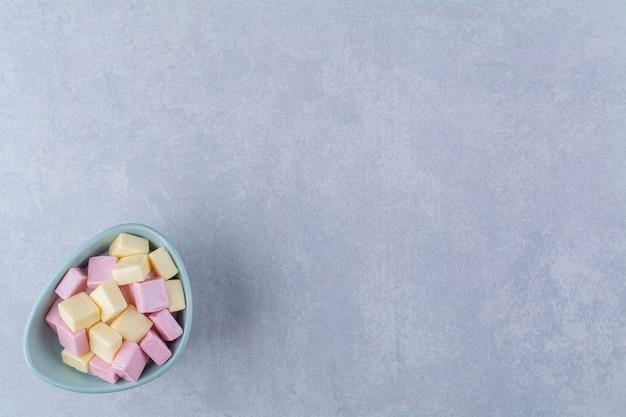 Een blauwe kom vol roze en gele zoete zoetwaren pastila