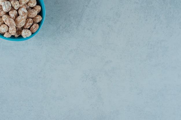 Een blauwe kom vol zoete heerlijke peperkoek op witte ondergrond