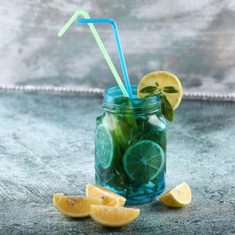 Een blauwe mojitokruik met citroen en munt op glanzende achtergrond met gele en blauwe pijpen.