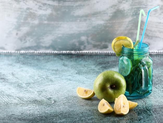 Een blauwe mojitokruik met citroen, groene appel en munt op glanzende achtergrond met gele en blauwe pijpen.