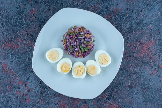 Een blauwe plaat van hardgekookte eieren met groenten.
