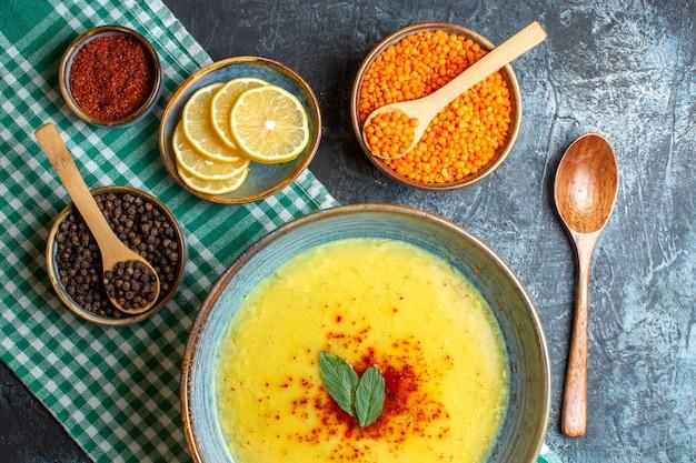 Een blauwe pot met smakelijke soep geserveerd met munt en peper op agreen gestripte handdoek naast gehakte citroen houten lepel en gele erwt verschillende kruiden op blauwe achtergrond