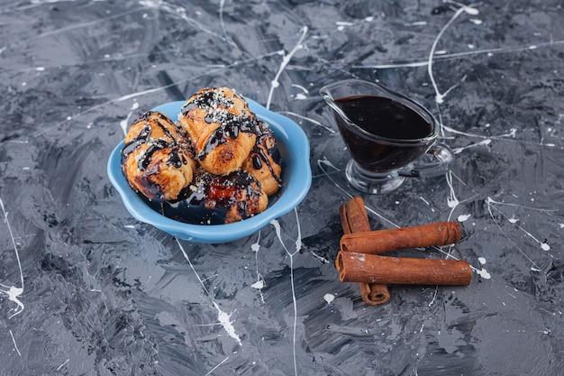 Een blauwe schaal vol mini croissants met chocoladedeklaag op marmeren ondergrond.