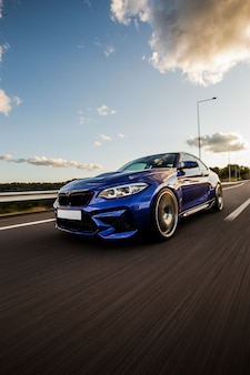 Een blauwe sport sedan testrit op de weg.