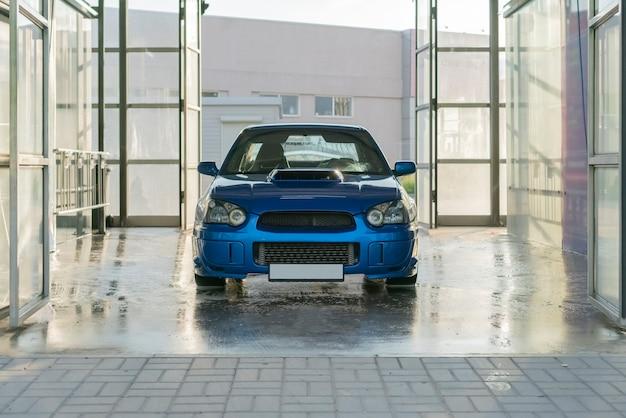 Een blauwe sportwagen in de zelfwasstationbox