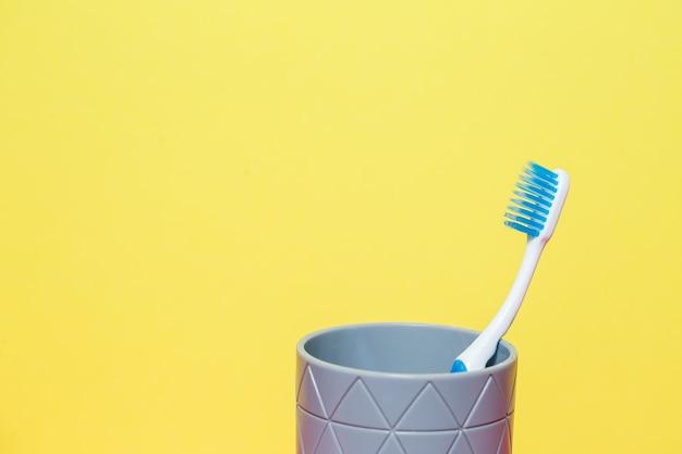 Een blauwe tandenborstel staat in een grijs glas. tandheelkundige zorgconcept