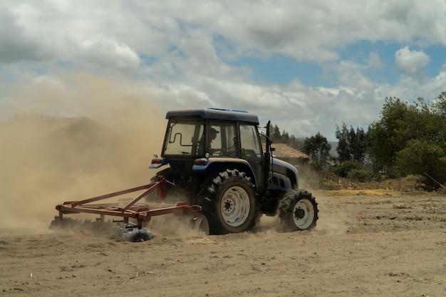 Een blauwe tractor die een gebied op een stoffige dag ploegt