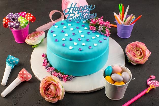 Een blauwe verjaardagstaart van bovenaf met snoepjes en gekleurde decors rondom