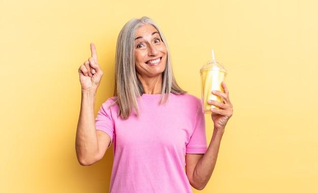 Een blij en opgewonden genie voelen na het realiseren van een idee, vrolijk vinger opsteken, eureka! en een milkshake vasthouden Premium Foto