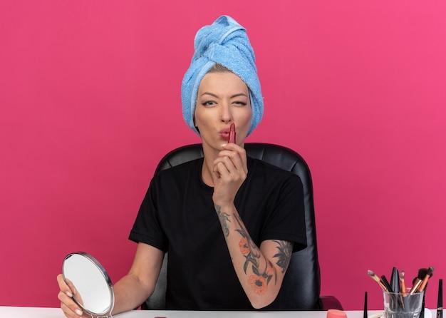 Een blij geknipperd jong mooi meisje zit aan tafel met make-uptools gewikkeld haar in een handdoek die lippenstift op een roze muur toepast