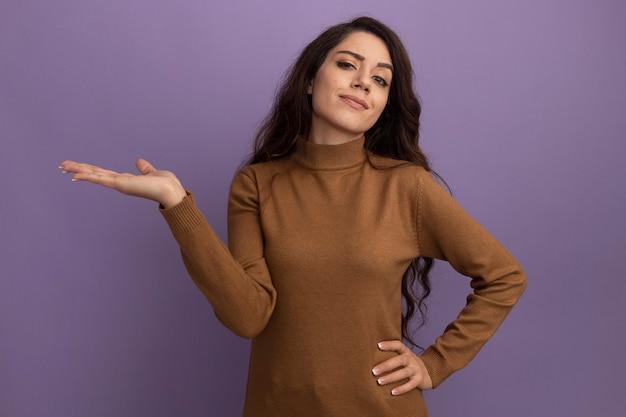 Een blij jong mooi meisje met een bruine coltrui die doet alsof ze iets vasthoudt en de hand op de heup zet, geïsoleerd op een paarse muur