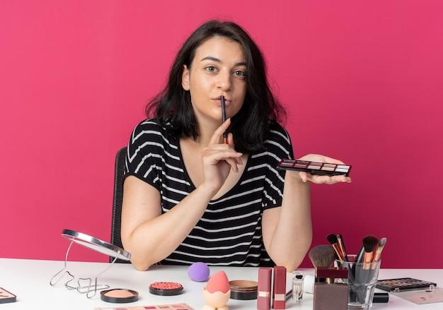 Een blij jong mooi meisje zit aan tafel met make-uphulpmiddelen die oogschaduw aanbrengen met een make-upborstel die een borstel op lippen zet die op een roze muur is geïsoleerd