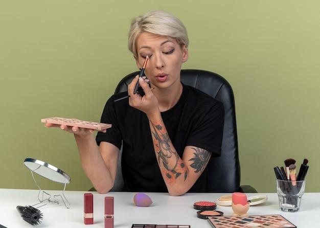 Een blij jong mooi meisje zit aan tafel met make-uphulpmiddelen die oogschaduw aanbrengen met een make-upborstel die op een olijfgroene muur is geïsoleerd