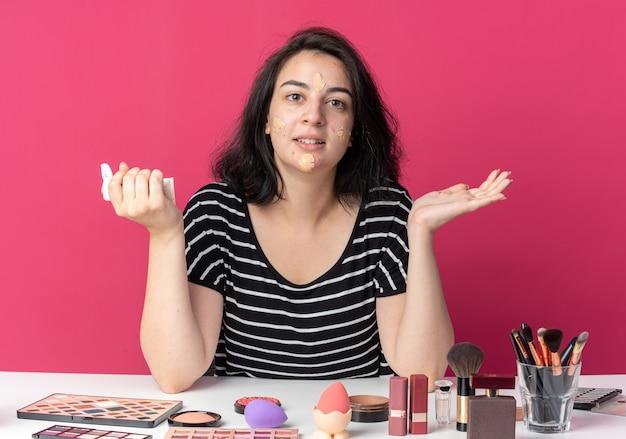 Een blij jong mooi meisje zit aan tafel met make-uptools die ton-upcrème aanbrengt die handen verspreidt die op roze muur zijn geïsoleerd
