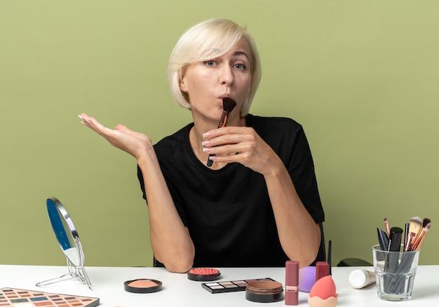Een blij jong mooi meisje zit aan tafel met make-uptools met een poederborstel die de hand verspreidt op een olijfgroene muur