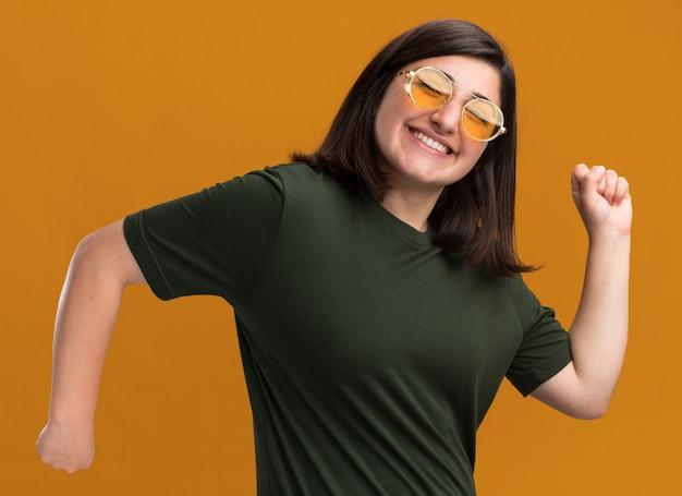 Een blij, mooi blank meisje met een zonnebril staat zijwaarts en houdt de vuisten geïsoleerd op een oranje muur met kopieerruimte