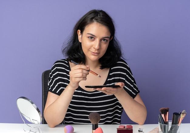 Een blij uitziend jong mooi meisje zit aan tafel met make-uptools die oogschaduw aanbrengen met een make-upborstel geïsoleerd op een blauwe muur blue