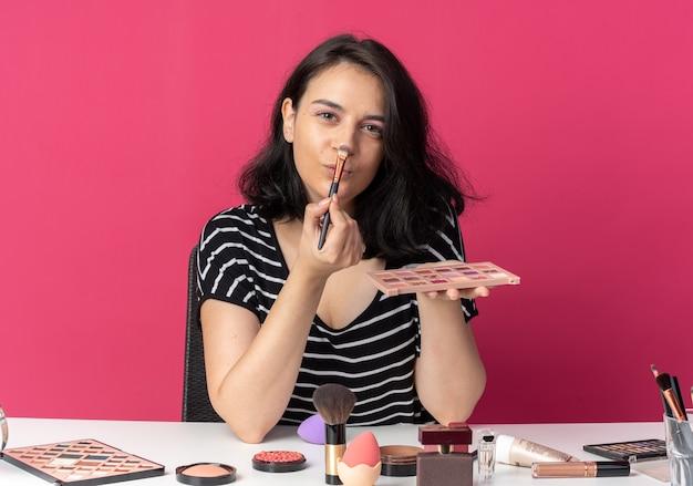 Een blij uitziend jong mooi meisje zit aan tafel met make-uptools die oogschaduw aanbrengen met een make-upborstel geïsoleerd op een roze muur pink