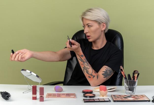Een blij uitziende jonge, mooie meid zit aan tafel met make-uptools die eyeliner vasthouden aan de zijkant geïsoleerd op een olijfgroene muur