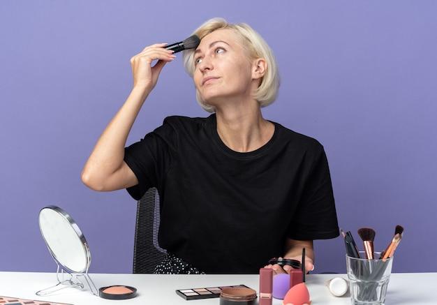 Een blij uitziende jonge, mooie meid zit aan tafel met make-uptools die poederblush toepassen met een poederborstel geïsoleerd op een blauwe muur