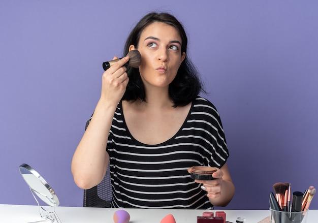 Een blij uitziende jonge, mooie meid zit aan tafel met make-uptools die poederblush toepassen op een blauwe muur
