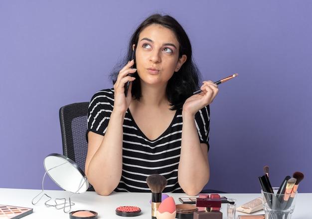 Een blij uitziende jonge, mooie meid zit aan tafel met make-uptools en spreekt op de telefoon met een make-upborstel geïsoleerd op een blauwe muur