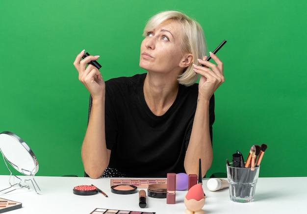Een blij uitziende jonge, mooie meid zit aan tafel met make-uptools met een poederborstel geïsoleerd op een groene muur