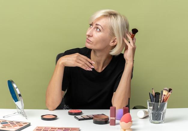 Een blij uitziende jonge, mooie meid zit aan tafel met make-uptools met een poederborstel geïsoleerd op een olijfgroene muur