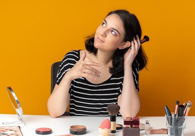 Een blij uitziende jonge, mooie meid zit aan tafel met make-uptools met een poederborstel geïsoleerd op een oranje muur