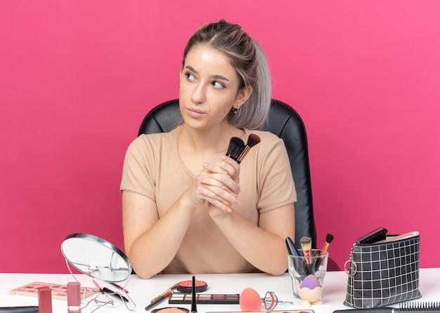 Een blij uitziende jonge, mooie meid zit aan tafel met make-uptools met een poederborstel geïsoleerd op een roze muur